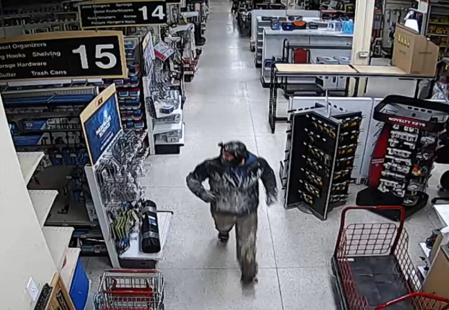 burglary suspect in dark coat and mask inside Ace Hardware